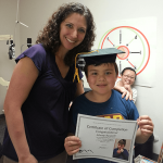 Johnny with his graduation cap and certificate