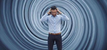 Man holding head with disorientating background