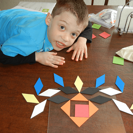 Zachary working on a visual exercise with blocks of different shapes and sizes